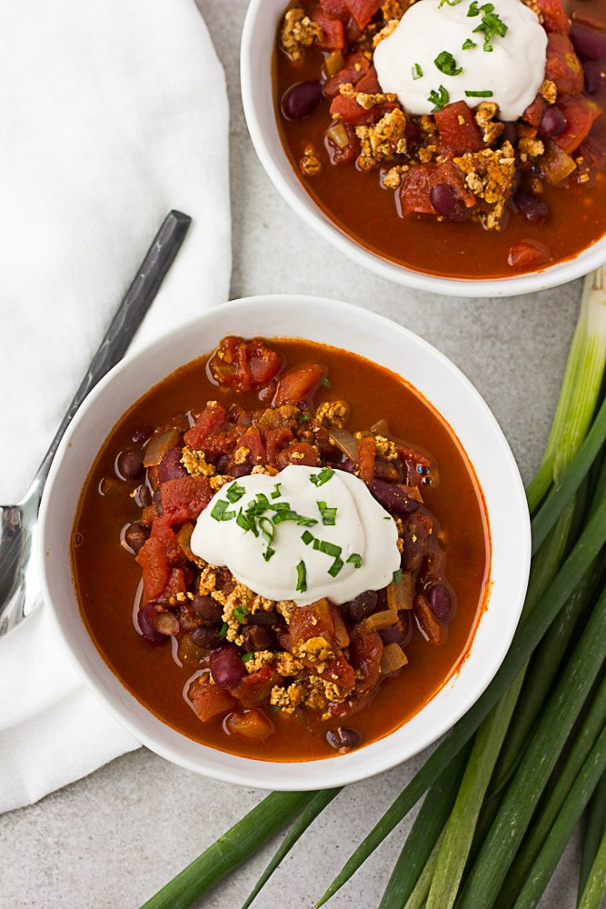 top down photo of 2 bowls of vegan chili with sour cream