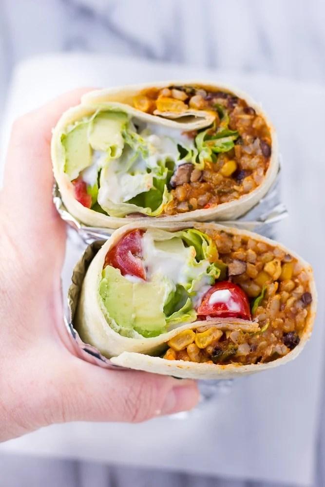 Hand holding instant pot vegan burritos
