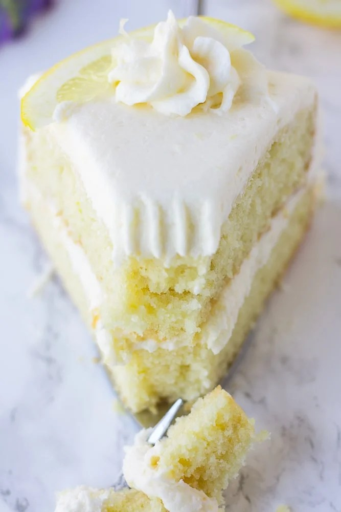 piece of vegan lemon cake with a fork taking a bite, close up.