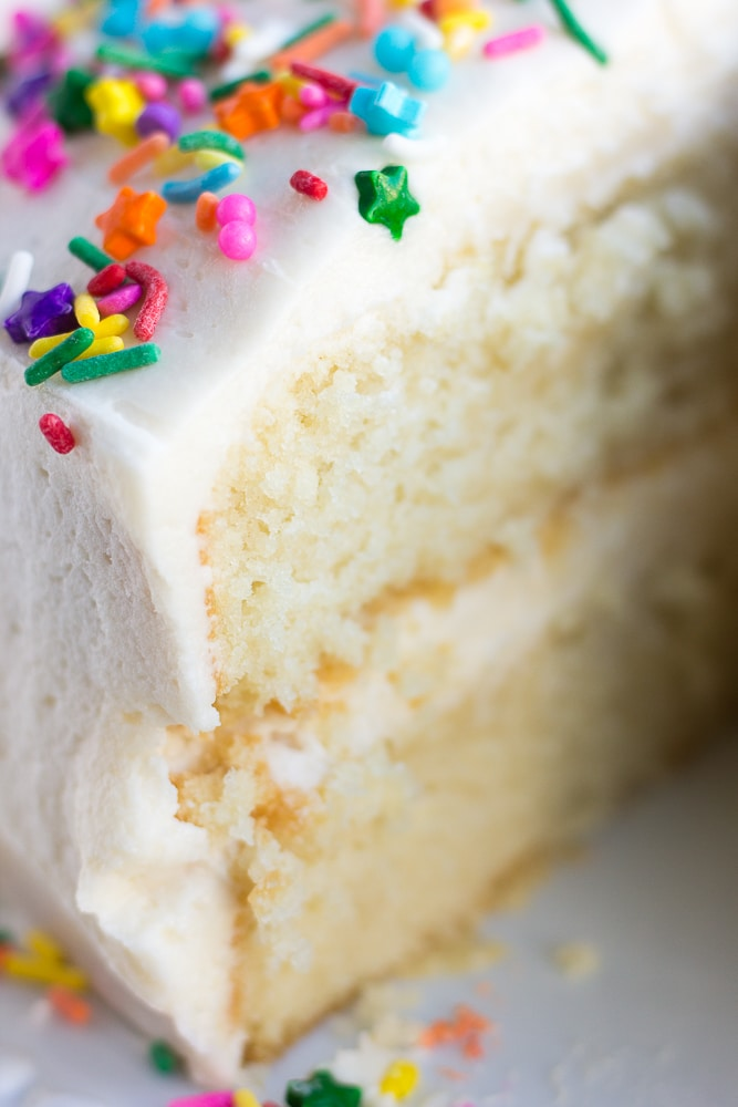 vegan frosting on double layer vanilla cake with sprinkles, close up photo.