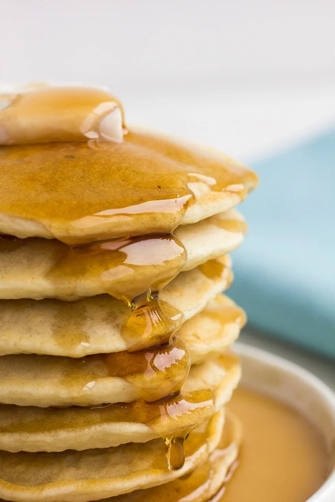 large stack of vegan pancakes with syrup and vegan butter