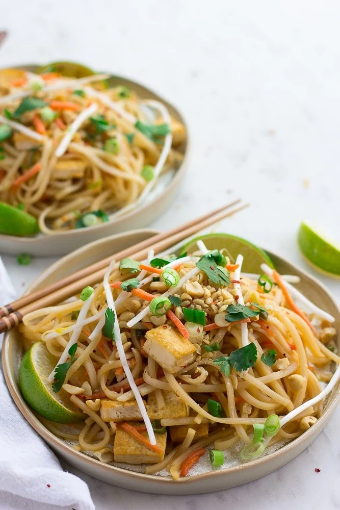 two plates with vegan pad thai on it with chopsticks