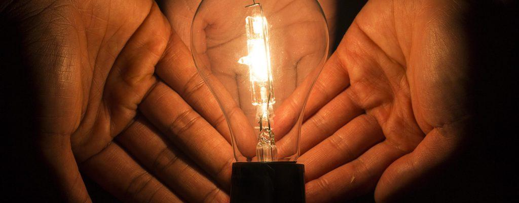 Hands Surrounding a Lightbulb