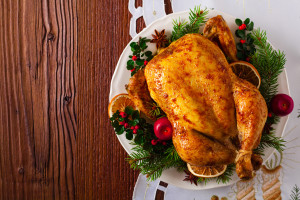 Roasted whole chicken with Christmas decoration. Wooden background. Top view.