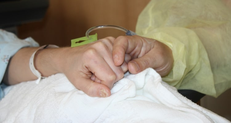 Ashley Quiñones holds the hand of her kidney donor, Jeremy Morris