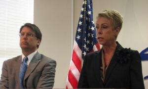 State Auditor Beth Wood describes the results of her audit of the state Medicaid program, while Governor Pat McCrory listens.