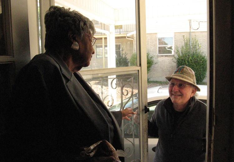 Millie Veasey stands in the doorway of her home, a smiling man in the doorway looks in. .