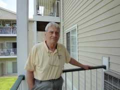 Jack Gregory stands on the porch of his new home at Carolina Springs Apartments, in Carrboro. Photo: Taylor Sisk.