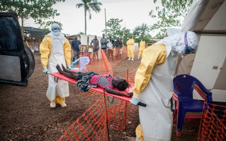 The MSF Ebola Treatment Centre. Two medical staff are bringing in a weak patient who has been in contact with people infected with Ebola to the admission area.