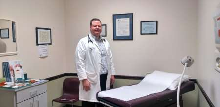Brian Forrest, MD, stands in an exam room in his Apex office