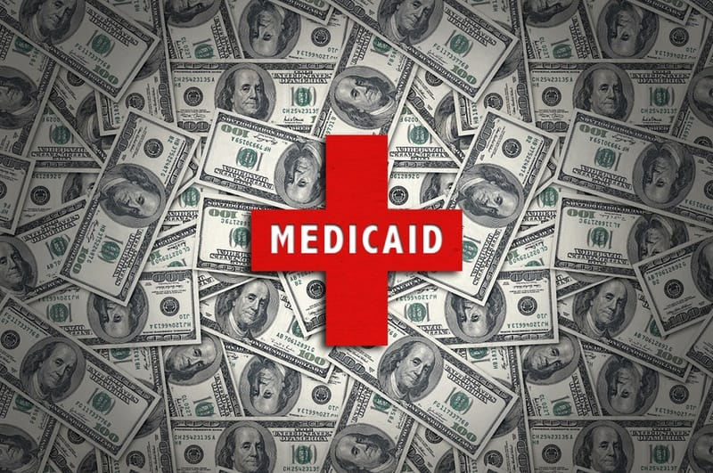 shows a red cross with the word Medicaid printed on it, in front of a pile of dollar bills. For Medicaid transformation