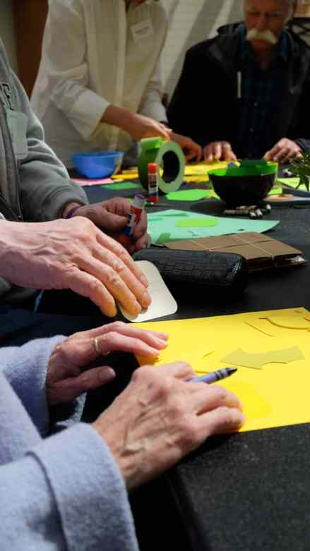 A docent helps group members as they make collages during one of their days out at the Nasher.