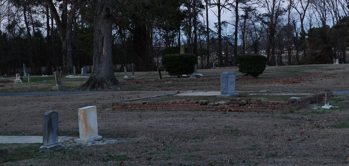 Photo shows decayed brick walls and fallen headstones.
