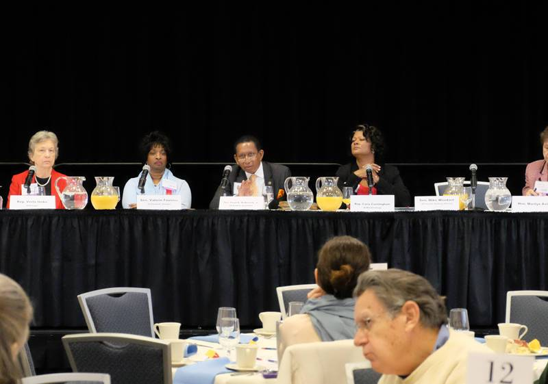 shows five peopel sitting at a long table on a dias, one is speaking.