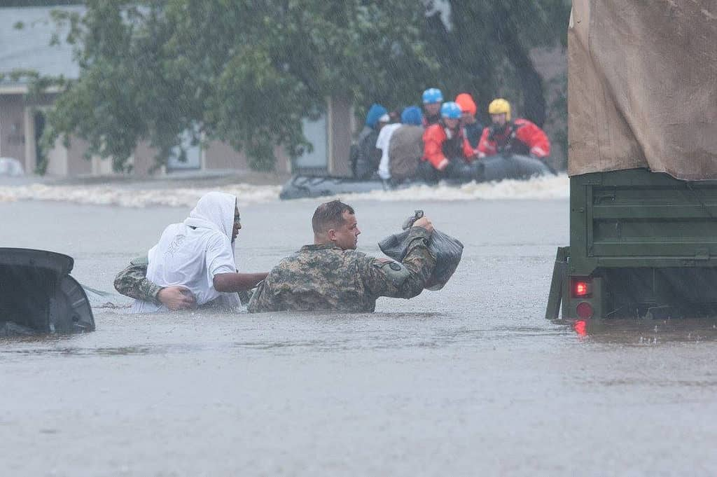 photo shows national guard member leading civilian throughflood waters to a waiting truck