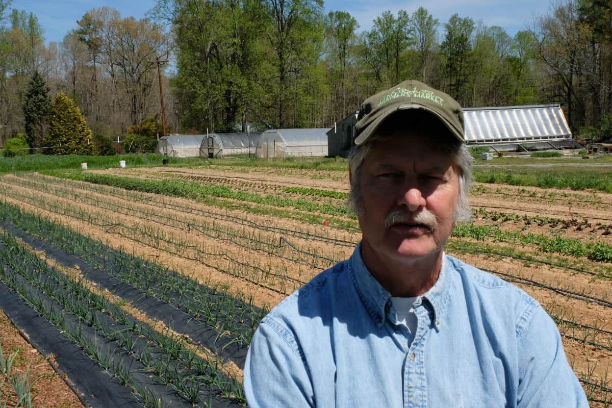 Alex stands in front of rows of small green vegetables, his face shaded from the sun by a baseball cap.