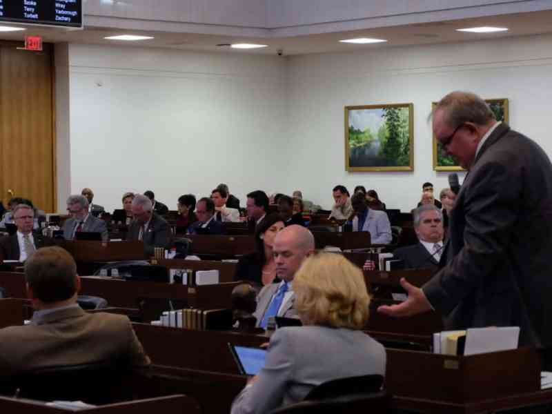 Rep. Chuck McGrady checks his notes as he makes the argument on the House floor for the Raise the Age bill.