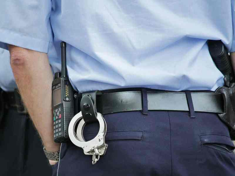 shows the back of a police officer, with handcuffs visibly prominent