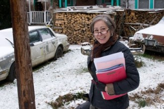 photo shows woman holding a stack of files, standing in a snowy yard in front of a house with a large woodstack in front of it