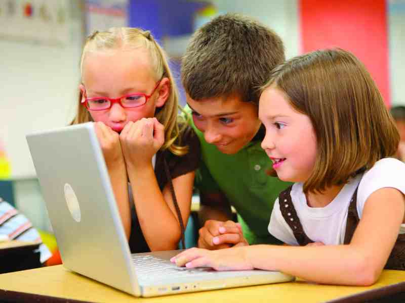three children with a laptop computer, their expressions show enthusiasm and excitement.