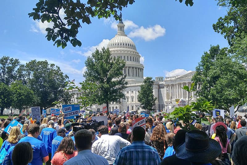 photo of crowd holding signs with the US Capitol in the background