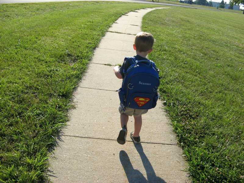 a little boy walks away from the camera with an enormous backpack on his back