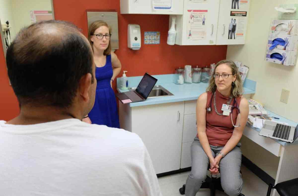 We see the back of a man's head and the two women talking to him. The clinic cares for patients in the uninsured gap and racial disparities in access to care.