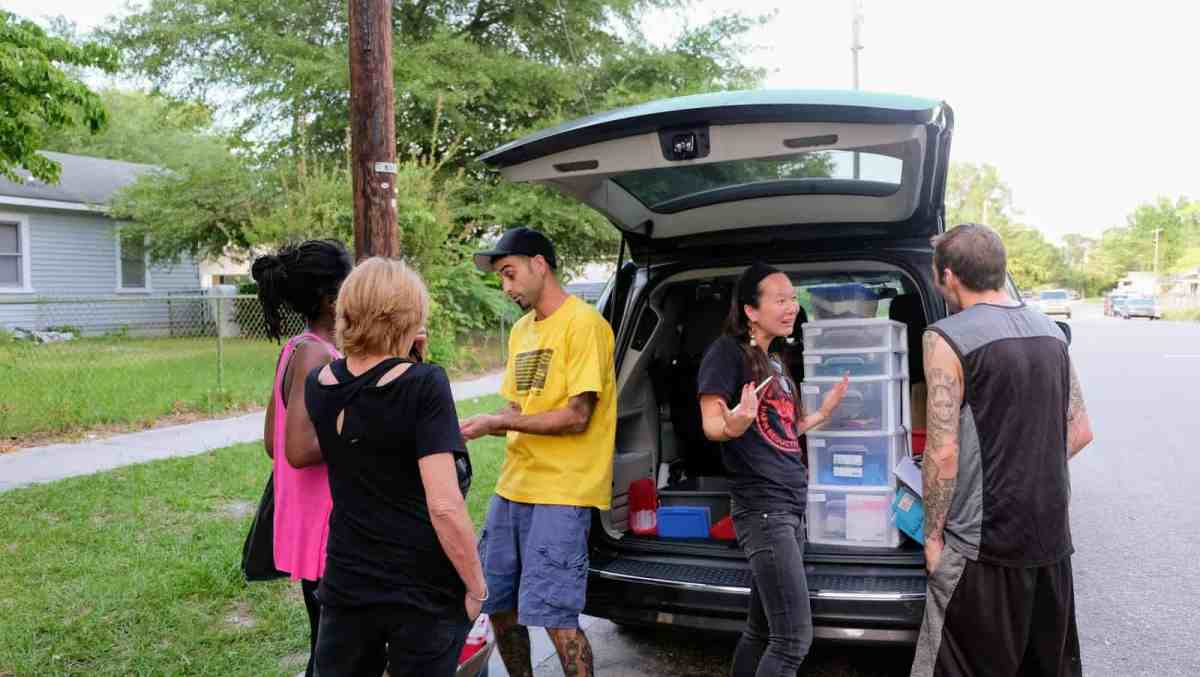 Shows five people gathered around the back of a van, the hatch is open, showing supplies inside.