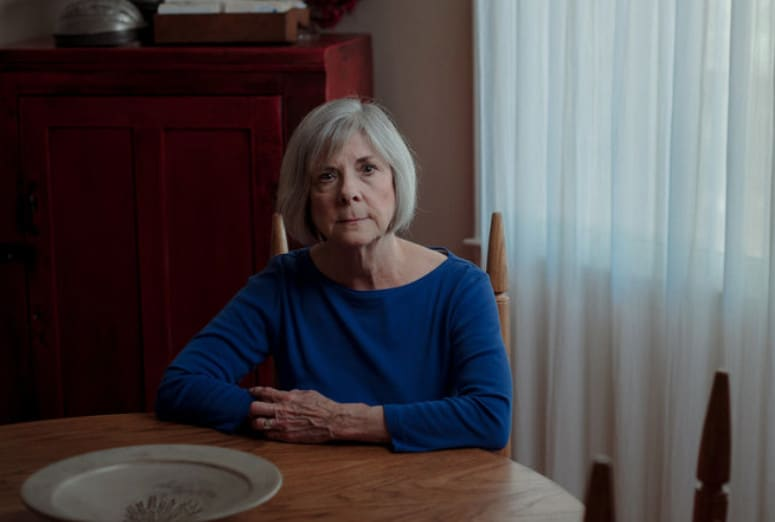 shows older white woman sitting at her table