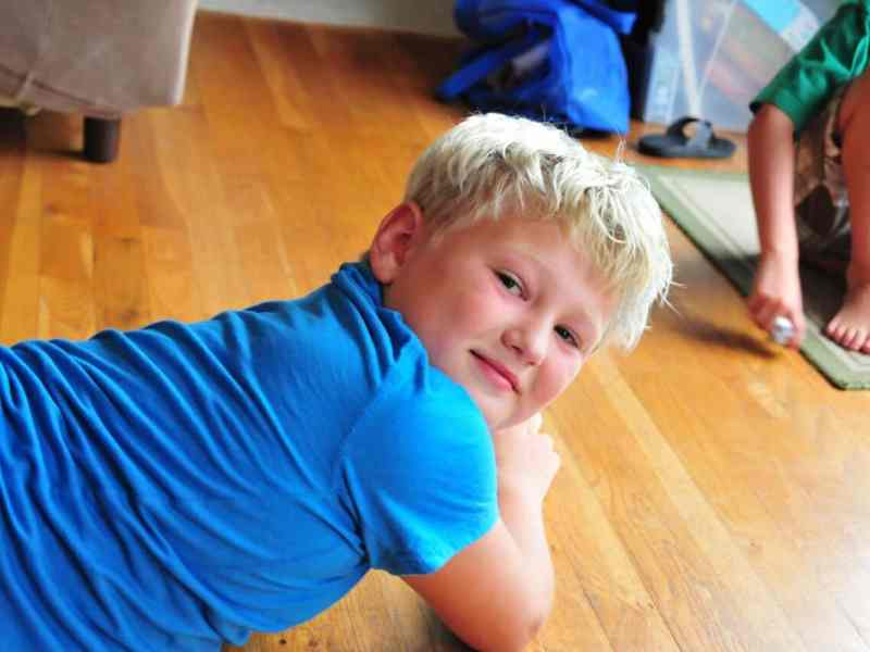 shows a boy with rosy cheeks laying on the floor, looking over his shoulder at the camera and smiling.