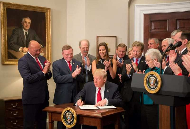 shows Trump at a desk signing while people around him applaud