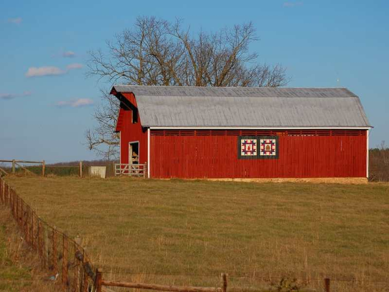 red barn on a hillside, next to a field of grass. It's an analogy for rural health or the rural-urban divide.