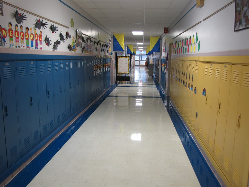 shows an empty hallway, lined with lockers, blue on one side, yellow on the other side