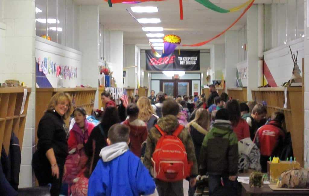 shows a crowded hallway filled with kids with backpacks.