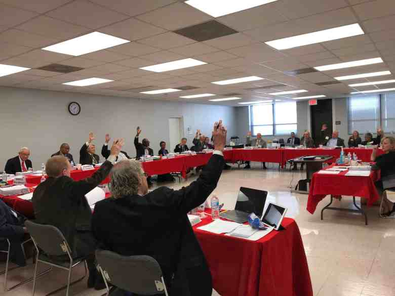 shows people sitting at long meeting tables, with hands raised commenting on new board members for Cardinal Innovations