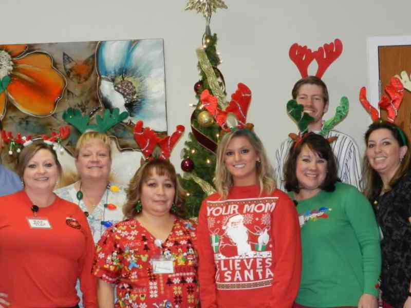 Shows a group of people wearing medical uniforns, along with christmas sweaters, etc and also wearing silly reindeer antlers on their heads.