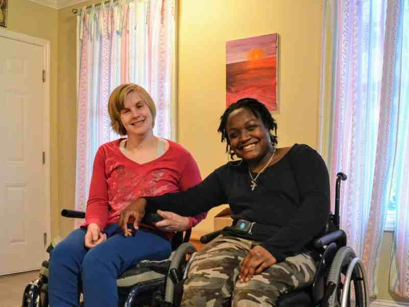 Shows two young women, both in wheelchairs, holding hands and smiling at the camera.