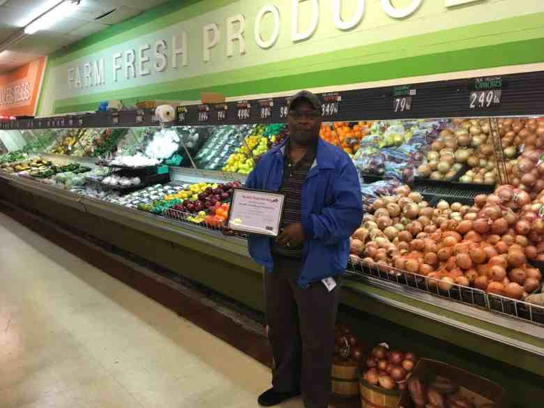 A man stands holding a certificate in front of display of fruits and vegetables in a store.