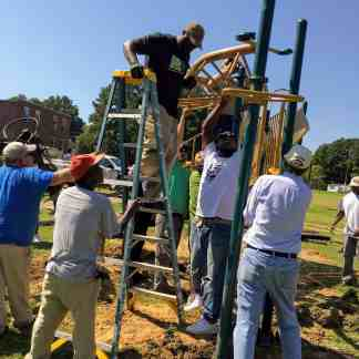 a group of men strain to put the top pieces onto a jungle gym