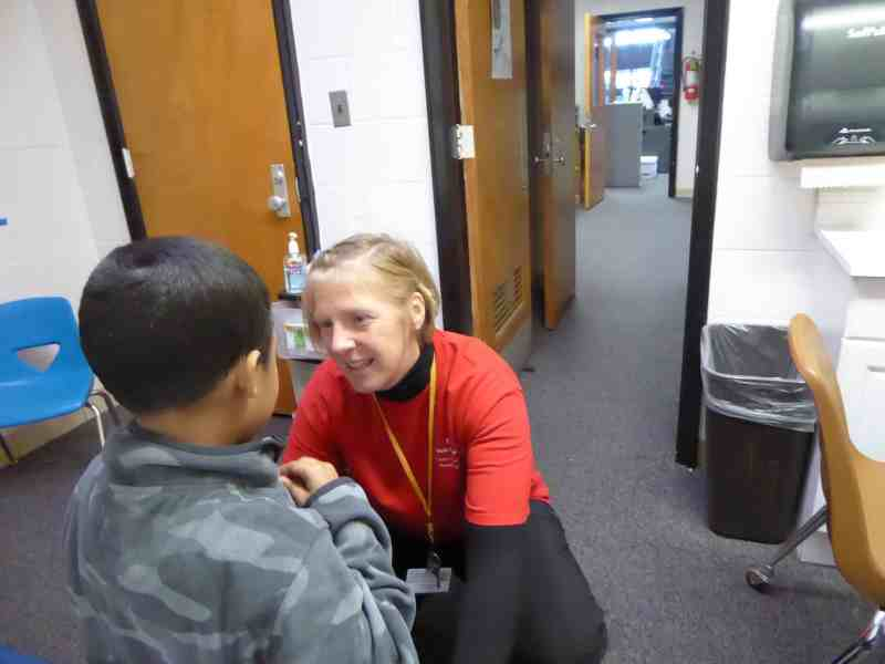 a school nurse squats down to be at eye level with a little boy