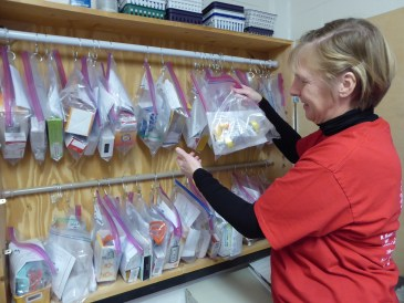 the school nurse stands at a wall cabinet filled with Ziploc bags filled with asthma inhalers.