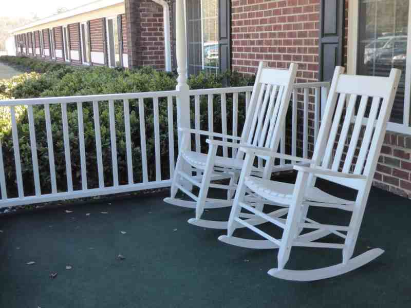 shows several empty rocking chairs on a porch