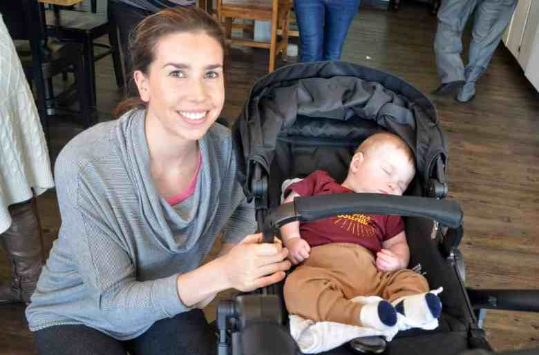 a woman squats next to her baby's stroller. She's smiling, he's napping.