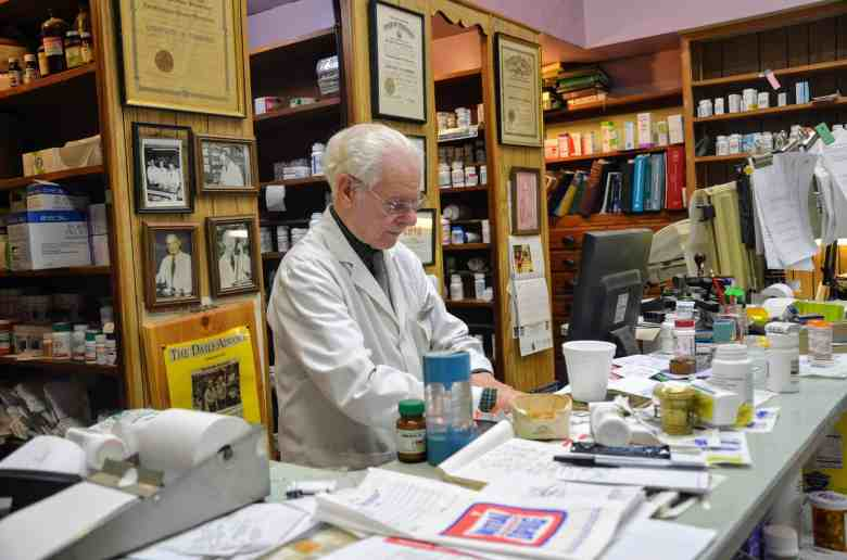 shows a man standing at a cluttered counter in a pharmacy