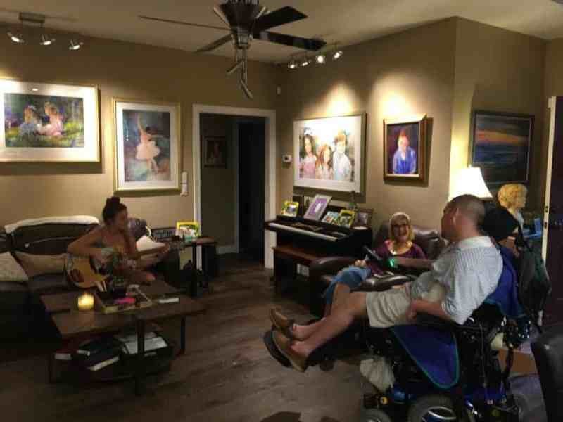 shows a young man in a wheelchair with other family members, one is playing a guitar