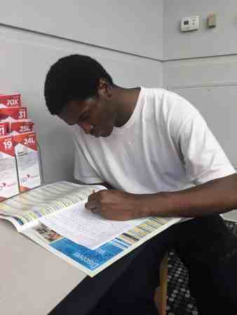 A young African American man sits at a table, writing in a workbook.