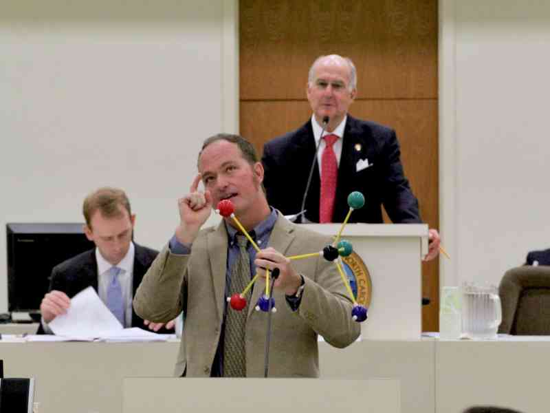 """a man stands at a podium, holding a model of a molecule, and gestures to show he's """"thinking"""""""