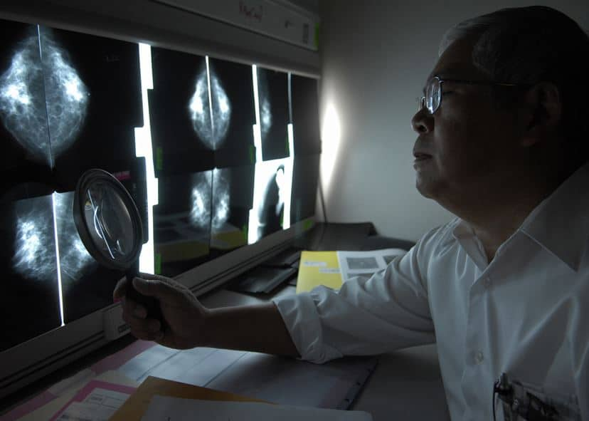 a doctor in a darkened room examines xrays of breast tissue to look for cancer.