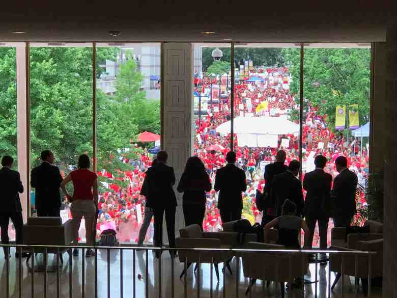 shows people in suits silhouetted against a window. outside is a large crowd of people wearing red