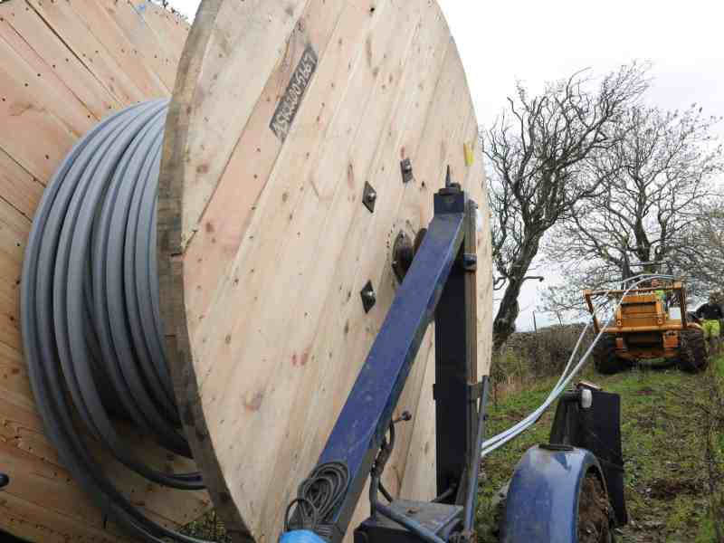 shows a reel of fiberoptic cable being pulled behind a tractor as the cable is being laid in the country side